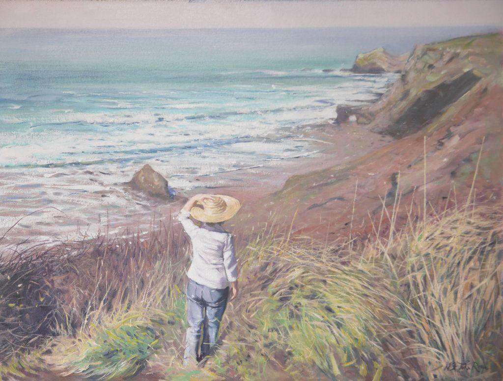 A young woman enjoying her walk along a Cornish cliff